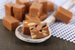 Many toffee in wooden spoon on napkin on wooden table