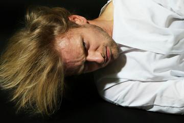 Mentally ill man in strait-jacket on black background