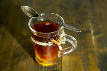 Hot beverage in glass cup with fruits and spices,