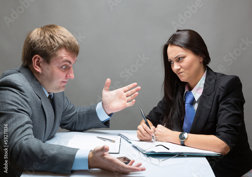 Two young caucasian office worker discussing contract