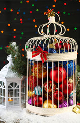 Christmas balls in decorative cage, on shiny background