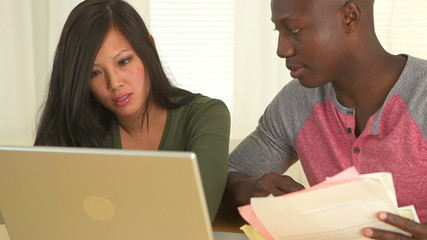 Asian and African American couple paying bills online