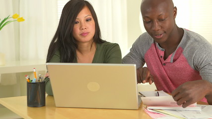 African American and Asian couple using computer to go over fina