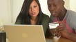 Asian and African American couple making online purchase with cr