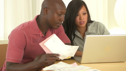 African American and Asian couple paying bills together
