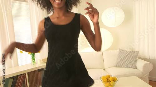 Cute black woman dancing in her living room