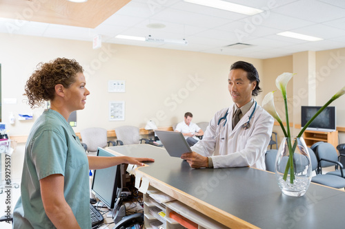 Nurse And Doctor Conversing At Hospital Reception