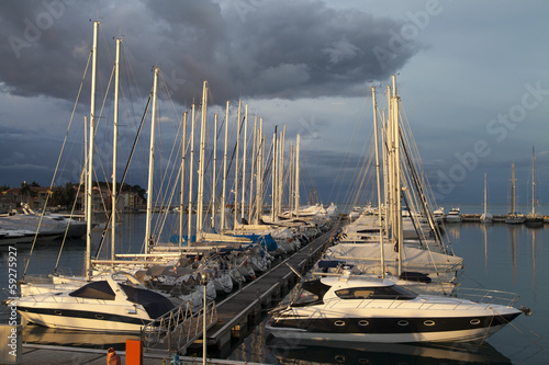 Sailing boats and yachts in a marina during the calm sunrise