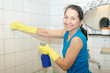 mature woman cleans bathroom