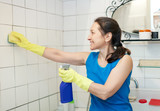 mature woman cleans tiled wall