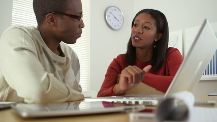 Black business colleagues using laptop computer together