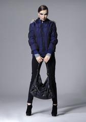full length Fashion girl posing in black dress with bag