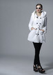 full length fashion model in white coat posing in studio