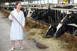 Happy woman in white robe sweeps floor in large farm