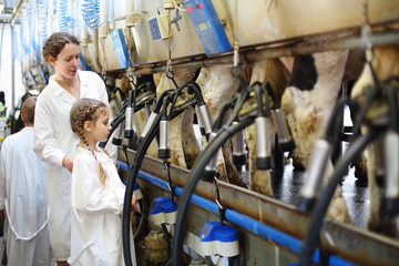 Mother and little daughter in white coats look at milking of cow