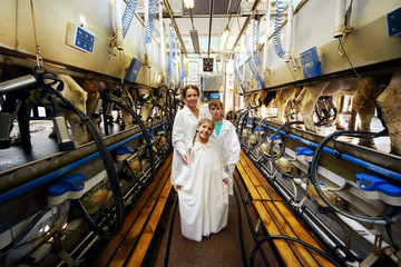 Mother, son and daughter in white robes and machines for milking