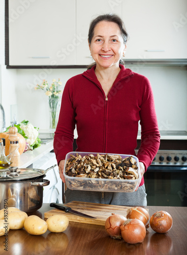 mature housewife holding  dried mushrooms