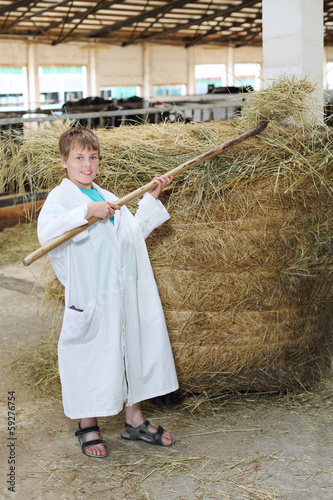 Smling boy in white coat loads hay by big pitchfork