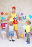 Three kids and facilitator play with balloons