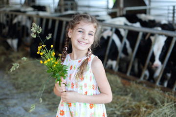 Happy little girl with wildflowers smiles and stands at cow farm