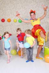 Three kids and holiday representative fun at children party.