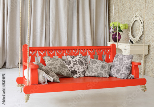 Big red wooden swing with pillows and  console mirror