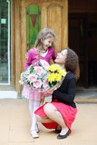 Happy young woman and daughter hold bunch of flowers