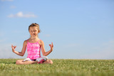 Happy little girl meditates on green field at sunny summer day.