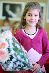 Happy beautiful girl with bunch of white flowers stands in class
