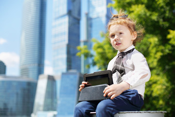 Little happy girl with tablet pc sits near tree near skyskrapers