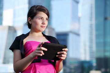 Beautiful girl in pink dress with tablet pc looks away
