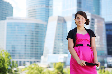 Smiling girl in pink dress with tablet pc stands near skyscraper
