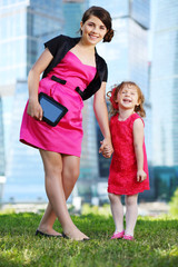 Beautiful girl with tablet pc and little laughing girl stand