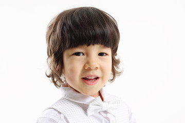 Face of little cute smiling boy in bow-tie on white background.