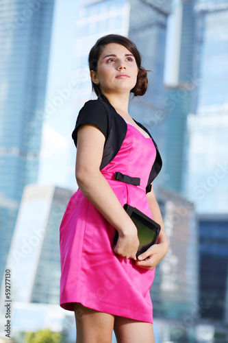 Happy girl in pink dress with tablet pc stands and looks up
