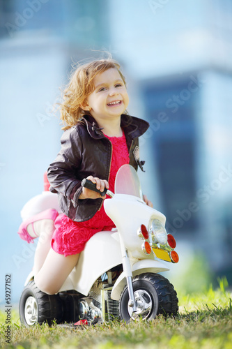 Little happy girl in leather jacket sits on toy motorbike