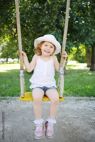 Little cute girl sits on swing at playground in park