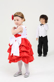 Little pretty girl in beautiful dress stands and boy stands