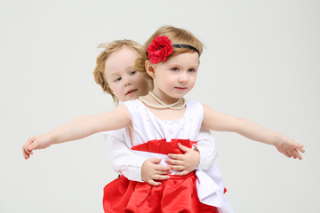 Little boy embraces beautiful girl with outstretched arms