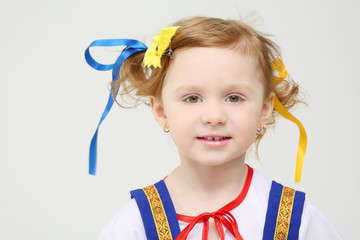 Little girl in Russian folk costume smiles on white background.