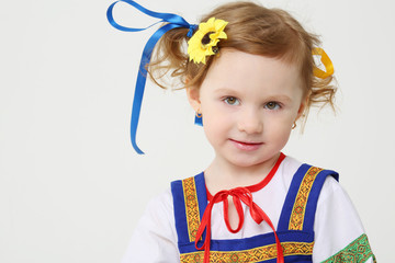 Little girl in Russian folk costume poses on white background.