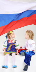 Little boy and girl in folk costumes look at russian flag