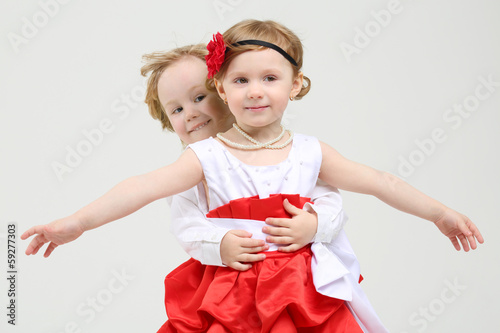 Little boy embraces happy girl with outstretched arms