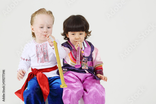 Two happy little boys in national costumes sit