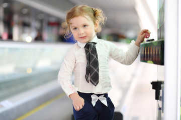 Little red hair girl in shirt and tie stands near game machine