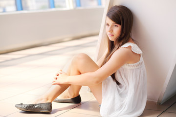Cute dreaming girl in white blouse sits on floor and looks away.