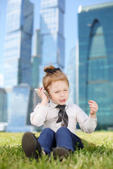Little cute girl in tie sits on grass and talks by cell phone