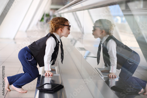 Little barefoot girl sits on floor in gallery near glass wall