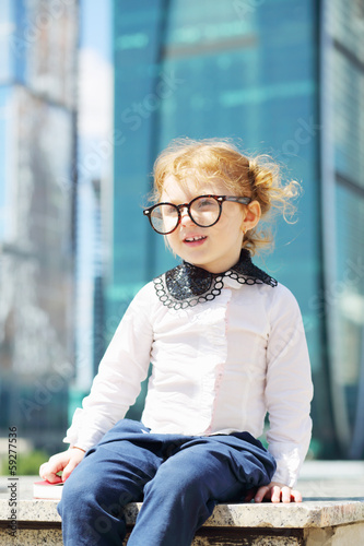 Little cute girl in glasses sits on border near skyskraper