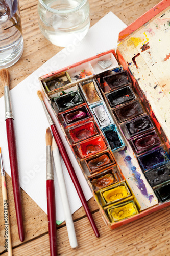 Watercolor paint box and brushes for painting .